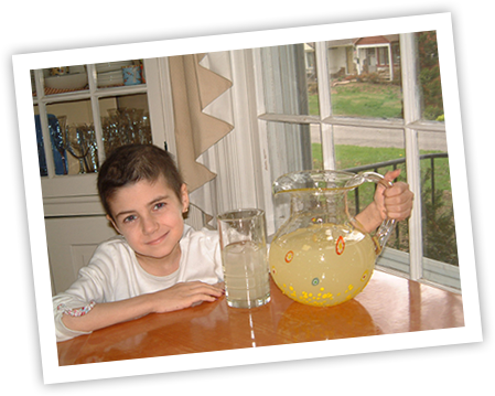 Alexandra Scott At A Kitchen Table With Pitcher Of Lemonade