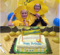 Children with lemon masks standing behind a birthday cake