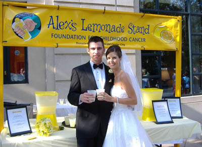A couple in wedding attire in front of ALSF stand