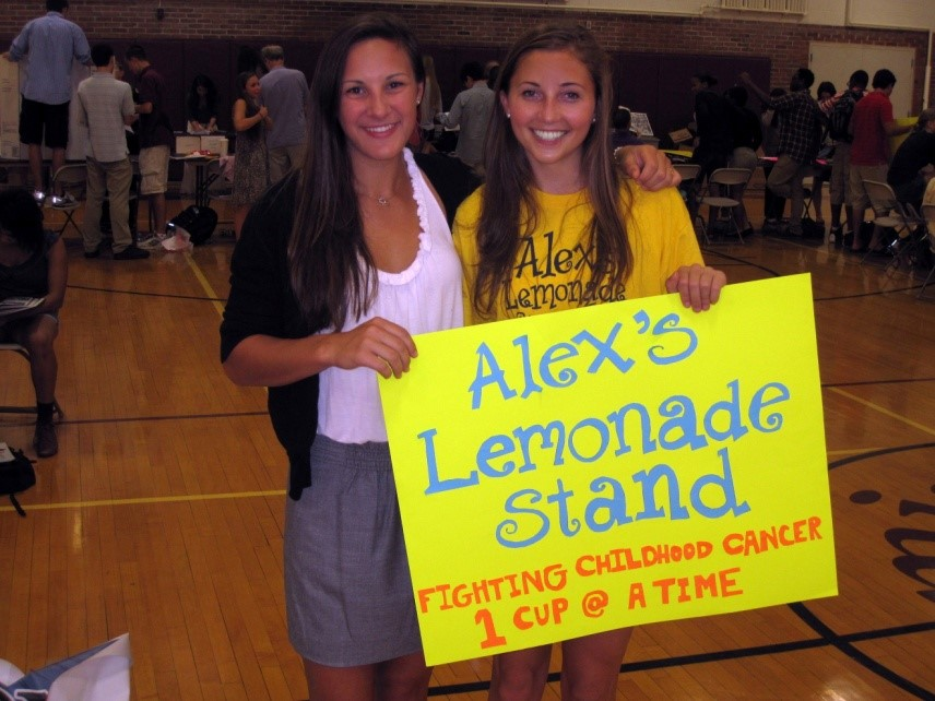 Two Lemon Club Students Holding Alex's Lemonade Sign
