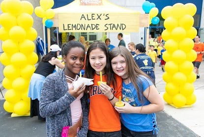 Three children in front of an Alex's Lemonade Stand